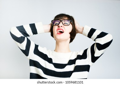 beautiful young woman in hysterics, short haircut, wears a sweater, studio photo on the background