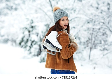 beautiful young woman with ice skates go to the rink