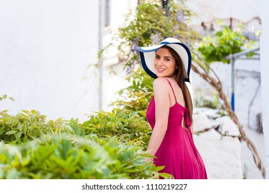 Beautiful young woman in idyllic mediterranean garden with sun hat and smiling happy at camera.