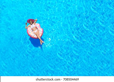 Beautiful young woman with inflatable donut in swimming pool