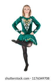Beautiful young woman in Irish dance green dress jumping isolated on white