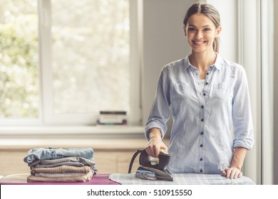 Beautiful young woman is ironing clothes, looking at camera and smiling