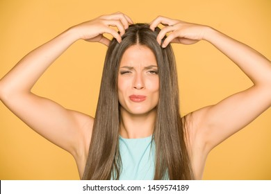 Beautiful young woman with itchy scalp on yellow background