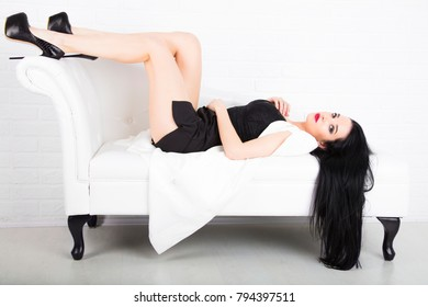 the beautiful young woman in a jacket on a white sofa