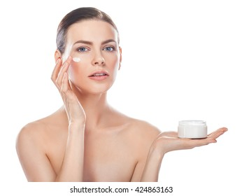 beautiful young woman with jar of cream and cosmetic cream on a cheek isolated on white with copy space