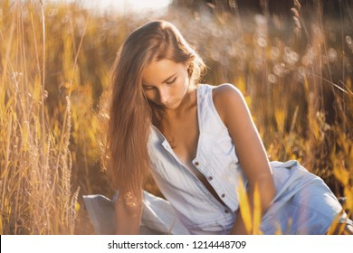 Beautiful young woman in jean sundress sitting relxed in a field of tall grass on sunset and reading a book
