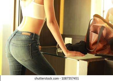 Beautiful young woman   with Jeans and underwea white standing in front of the mirror