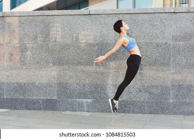 Beautiful young woman jumping against gray wall, copy space. Freedom spirit concept, copy space