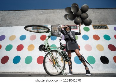 Beautiful young woman jumping with a lot of black baloons and Guy with bicycle posing on the street and looking at she.