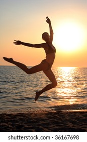 Beautiful young woman jumping on the beach at sunset