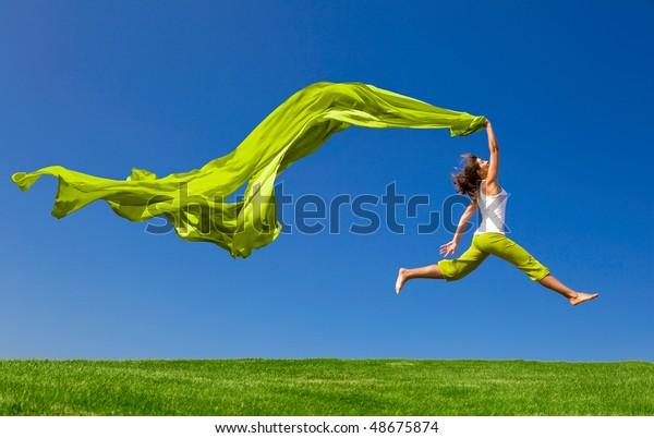 色と組織を持つ緑の草地で跳び上がる美しい若い女性