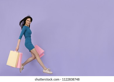 beautiful young woman jumping with shopping bags