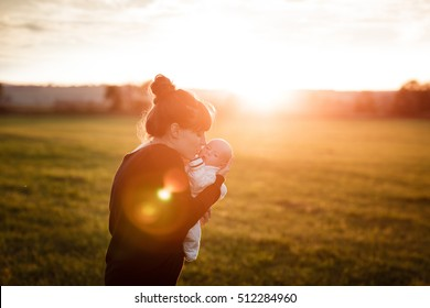 Beautiful young woman kisses her adorable little son at sunny in the meadow in sunset. Young mother holding her newborn baby. Mother and new born boy having good time in the nature. Color toned image.