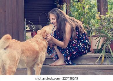 beautiful young woman kissing her dog labrador