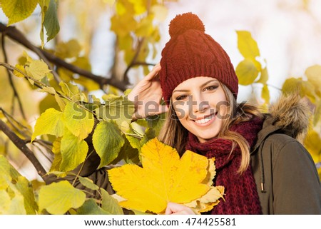 Beautiful Young Woman In Knitted Dark Red Beanie Hat With Pompom And Scarf Outdoors In Park
