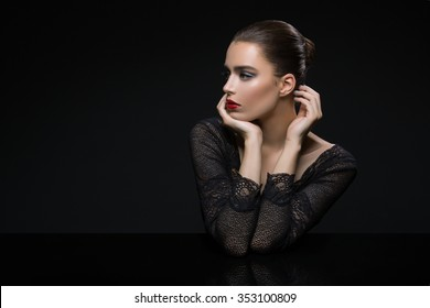 Beautiful young woman in lace top with red lips touching face. Over black background. Copy space.