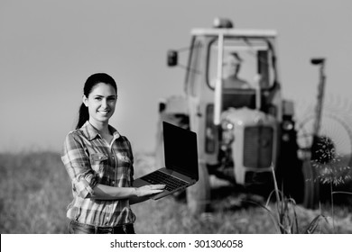 Beautiful young woman with laptop standing in the field with tractor in background, black and white image