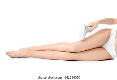 Beautiful young woman with laser epilator on white background