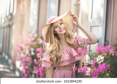 Beautiful young woman is laughing during her walk outsitde in the city. She is wearing a hat and pink summer dress, standing next to the pink flowers.