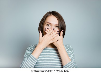 beautiful young woman laughs covering her mouth with her hand, isolated on background, studio photo
