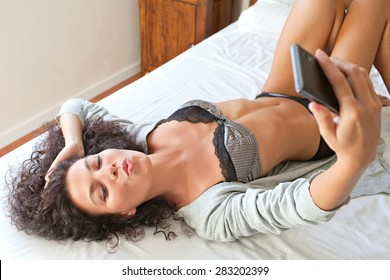 Beautiful young woman laying on bed at home, holding up a smartphone to take selfies pictures of herself, blowing kisses networking on line in social media, aspirational living technology, interior.