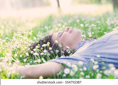 Beautiful young woman laying on a green grass with white flowers in a park.