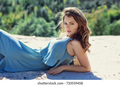 Beautiful young woman laying on white sand beach with wind blowing hair and dress. Woman relaxing on the beach