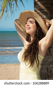 A beautiful young woman leaning against palm tree on a tropical beach wearing a straw hat.