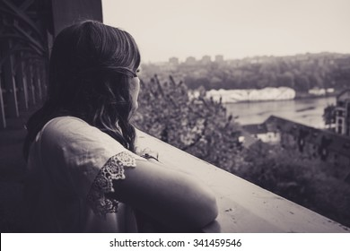 Beautiful young woman leaning on the railings of the High Level Bridge, Newcastle Upon Tyne, staring out at the River Tyne.  In black and white, giving the image a dreamy look.