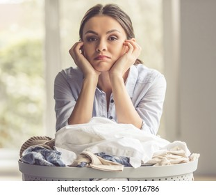 Beautiful young woman is leaning on the basin with laundry and looking at camera while standing at home