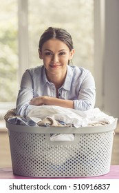 Beautiful young woman is leaning on the basin with laundry, looking at camera and smiling