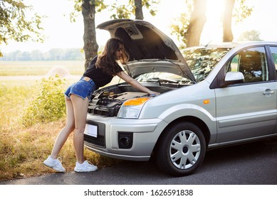 Beautiful young woman leaning over hood of broken car. Concept of problems with car