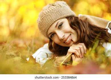 Beautiful young woman with leaves lying on the grass in autumn park