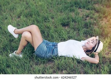 A beautiful young woman lies in a green meadow.