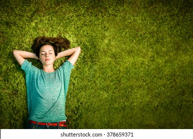 beautiful young woman lies on green moss relaxing with eyes closed and hands behind his head