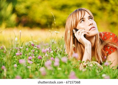 Beautiful young woman lies on green summer meadow among clover and talks by mobile phone.