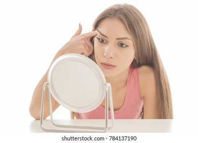 beautiful young woman lifting her eyebrows in front of a mirror