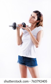 A beautiful young woman lifting weight and pointing on gym equipment