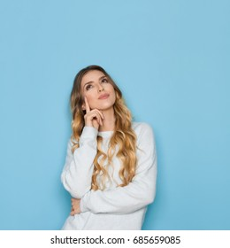 Beautiful young woman in light blue pastel sweater is holding hand on chin, looking up and planning. Waist up studio shot on blue background.