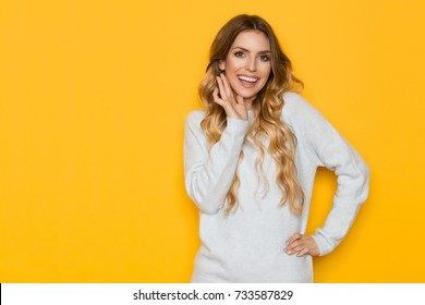 Beautiful young woman in light blue pastel sweater is holding hand on chin, smiling, and looking at camera. Waist up studio shot on yellow background.