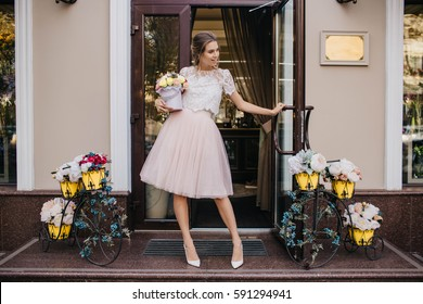 Beautiful young woman in light tulle skirt, on heels smiling on street with bouquet of flowers. Cheerful mood, walking, gift, present, fashionable, stylish model