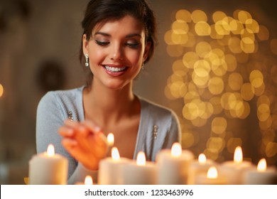 Beautiful young woman lighting candles in front of fireplace in a dark room with christmas lights.