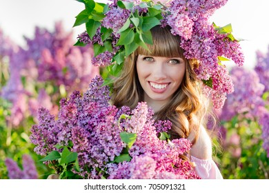 The beautiful young woman with a lilac wreath on her head holds a fragrant lilac bouquet in a lilac garden
