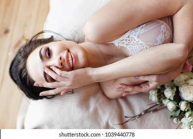 Beautiful young woman in lingerie lying on bed in the morning and laughing sincerely hiding face with hand. Sexy bride and bouquet