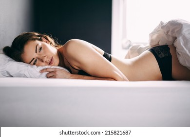 ae6b5c5665 Beautiful young woman in lingerie lying in her bed looking away thinking.  Thoughtful female model