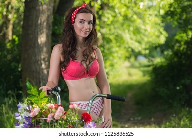 ad4acd2af6a0 Beautiful young woman in lingerie outdoors with bicycle and flowers