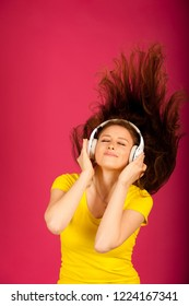 Beautiful young woman listen music and  dance over pink background
