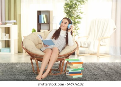 Beautiful young woman listening to audiobook at home