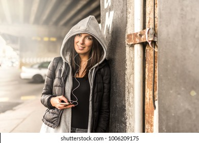 A beautiful young woman listening to music on her smartphone in a urban environment.