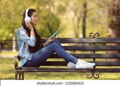 Beautiful young woman listening to music while resting in park